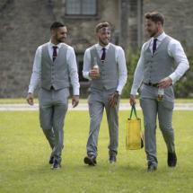 3 Groomsmen walking along the lawn at Dartington Hall