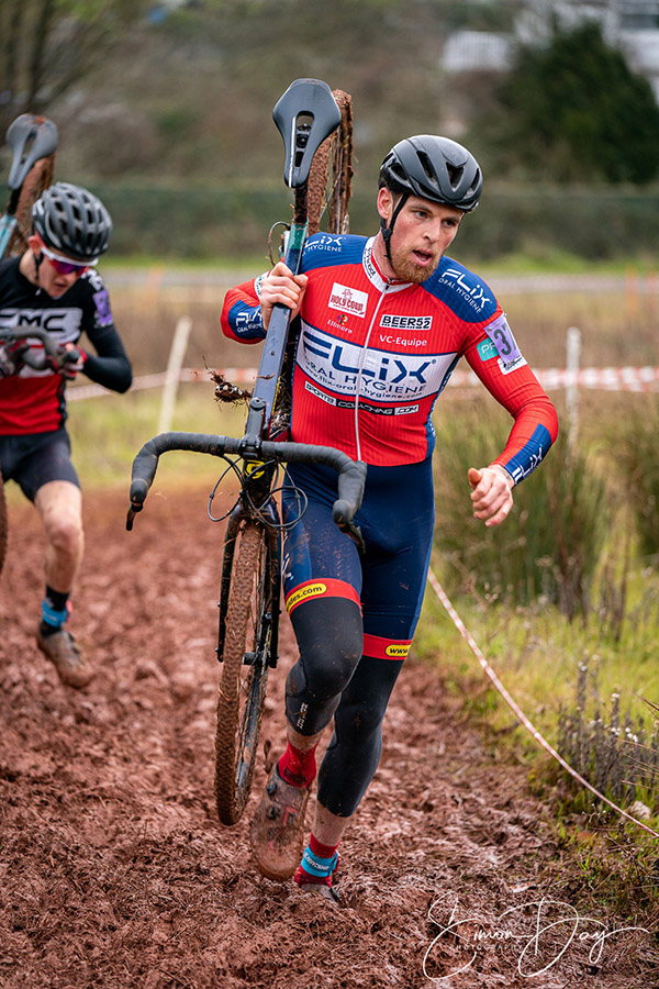 Carrying racing bike over muddy cycle race track