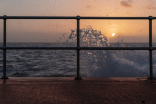 Teignmouth seafront with wave hitting wall at sunrise