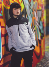 Portrait leaning against graffiti wall