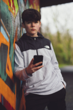 portrait photo leaning against graffiti wall with phone