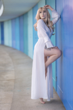 Model posed leaning against beach huts at Meadfoot beach in Torquay.