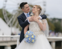 Bride and Groom on Torquay pier with big wheel in the background.