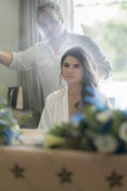 Bride looking through mirror has hair spray goes on