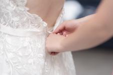 Wedding dress being put on.